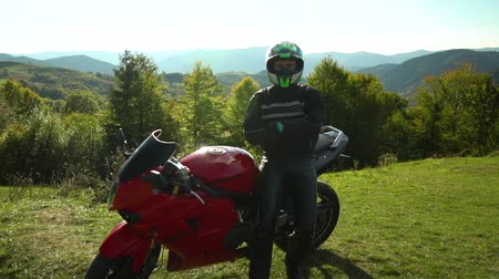 A guy on a motorcycle. Young handsome guy with his motorcycle in the mountains. The guy stands near his motorcycle and looks at the mountains. He is happy.