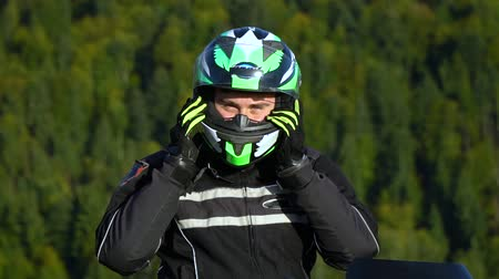 A guy on a motorcycle. Young handsome guy with his motorcycle in the mountains. Close-up. The guy takes off his helmet. Vídeos