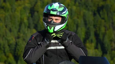 A guy on a motorcycle. Young handsome guy with his motorcycle in the mountains. Close-up. The guy puts on a helmet. Slow motion.