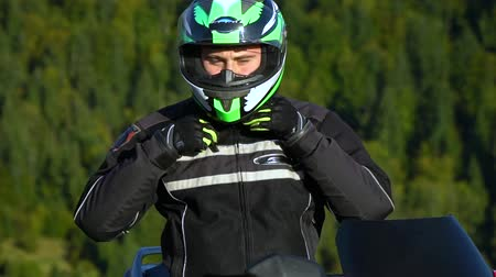 rider : A guy on a motorcycle. Young handsome guy with his motorcycle in the mountains. Close-up. The guy puts on a helmet. Stock Footage