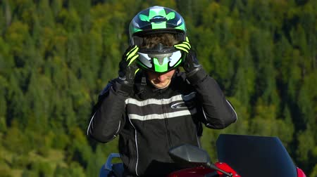 A guy on a motorcycle. Young handsome guy with his motorcycle in the mountains. The guy is resting. He drinks water. Close-up. The guy takes off his helmet.