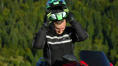 A guy on a motorcycle. Young handsome guy with his motorcycle in the mountains. The guy is resting. He drinks water. Close-up. Slow motion. Vídeos