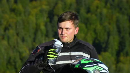 skútr : A guy on a motorcycle. Young handsome guy with his motorcycle in the mountains. The guy is resting. He drinks water. Close-up. Slow motion. Dostupné videozáznamy