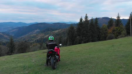 A guy on a motorcycle. Young handsome guy rides a motorcycle on a mountain road. The guy stands near his motorcycle and looks at the mountains. He is happy. Shooting from the quadcopter. Vídeos