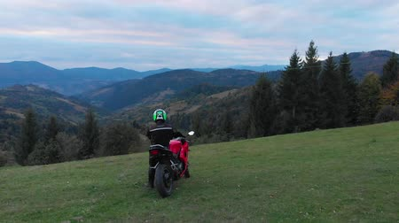 rider : A guy on a motorcycle. Young handsome guy rides a motorcycle on a mountain road. The guy stands near his motorcycle and looks at the mountains. He is happy. Shooting from the quadcopter. Stock Footage