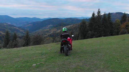 стенд : A guy on a motorcycle. Young handsome guy rides a motorcycle on a mountain road. The guy stands near his motorcycle and looks at the mountains. He is happy. Shooting from the quadcopter. Стоковые видеозаписи