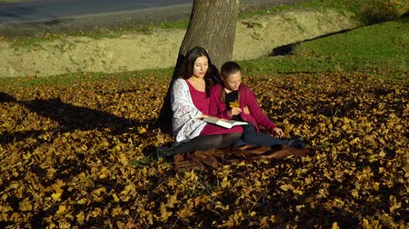 терпение : Mom and daughter sit under a tree and read a book. They talk nicely. Mom and daughter in the autumn forest. They are happy.