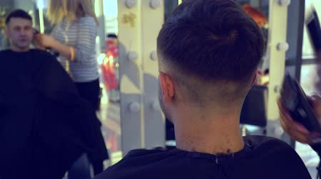 kartáč na vlasy : Beauty saloon. Barbershop. Stylist makes haircut to a young handsome guy. The guy sits in a chair and looks in the mirror. He is pleased. The stylist uses an electric shaver. Close-up.