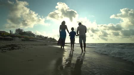 anne : Family walks on the beach. Parents walk with their son along the seashore. They are happy. The sun shines brightly. Silhouettes of people. Slow motion. Family happiness. Stok Video