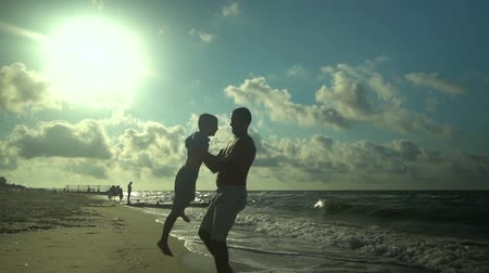 trusting : A young father walks with his son along the seashore. The sun shines brightly. Dad spins his son and throws him into the air. Family happiness. Trust relationship between father and son. Slow motion. Stock Footage