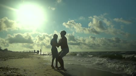 trusting : A young father walks with his son along the seashore. The sun shines brightly. Dad throws his son in the air. Family happiness. Trust relationship between father and son. Slow motion.