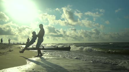 trusting : A young father walks with his son along the seashore. The sun shines brightly. Dad is spinning his son. Family happiness. Trust relationship between father and son. Slow motion.