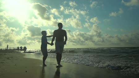 trusting : A young father walks with his son along the seashore. The sun shines brightly. They are talking. Family happiness. Trust relationship between father and son. Slow motion. Stock Footage