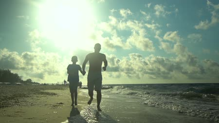 trusting : A young father runs with his son along the seashore. The sun shines brightly. They speak. Family happiness. Trust relationship between father and son. Slow motion. Stock Footage