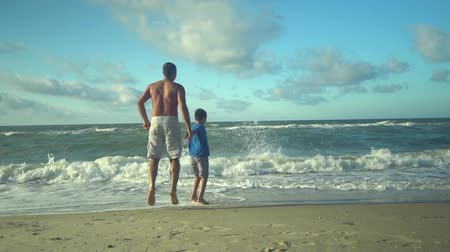 trusting : Young father riding with his son on the beach. The sun shines brightly. Dad and son are happy. Trust relationship between father and son. Slow motion. Stock Footage