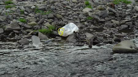 feiúra : Rubbish on the river. Garbage in a mountain river. Environmental pollution. Pollution of nature. Ecological catastrophy. Non-degradable plastic.