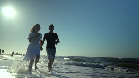 isabet : Young beautiful couple walking by the sea. Boy and girl. They are happy. The sun shines brightly. Slow motion. They run along the sandy beach. Silhouettes. The waves hit the shore.