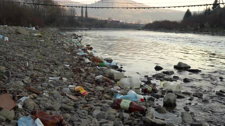 rothadó : Rubbish on the river. Garbage in a mountain river. Environmental pollution. Pollution of nature. Ecological catastrophy. Non-degradable plastic.