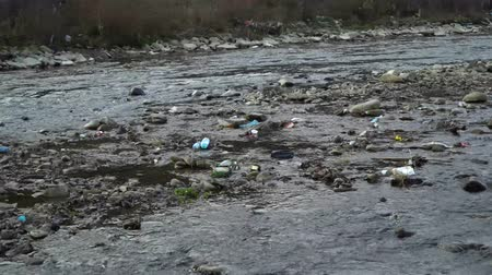 organizma : Rubbish on the river. Garbage in a mountain river. Environmental pollution. Pollution of nature. Ecological catastrophy. Non-degradable plastic.