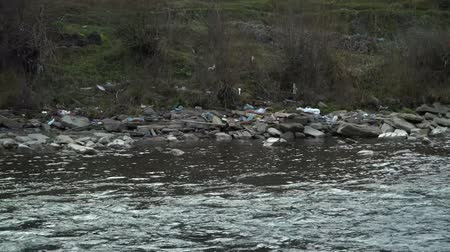 csúnyaság : Rubbish on the river. Garbage in a mountain river. Environmental pollution. Pollution of nature. Ecological catastrophy. Non-degradable plastic.