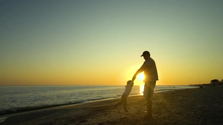 沿岸の : A young handsome man walks with his little daughter along the seashore at sunset. Dad takes the daughter in his arms. They are happy. Silhouettes against the setting sun. Slow motion.