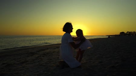 yakalamak : Young beautiful woman walks with her little daughter on the seashore at sunset. Mom takes her daughter in her arms. They are happy. Silhouettes against the setting sun. Slow motion.