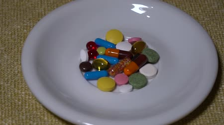 dispensing : Pills. Medication closeup. Pills. Medication closeup. A pile of multi-colored tablets lies on a white saucer. Biologically Active Additives and vitamins. Close-up. Slow motion.