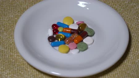 omega : Pills. Medication closeup. A pile of multi-colored tablets lies on a white saucer. Biologically Active Additives and vitamins. Close-up.