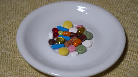 dispensing : Pills. Medication closeup. A pile of multi-colored tablets lies on a white saucer. Biologically Active Additives and vitamins. Close-up.
