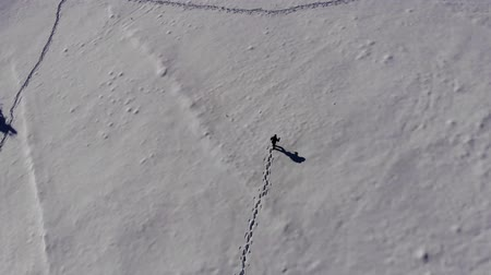 üst : A lone tourist walks through the snow in a mountain forest. Traveler in the winter snow-covered forest with a birds-eye view. Shooting on the quadcopter.