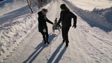 śnieżka : Young happy family having fun playing in a snowy forest. Parents roll their little son on a sled. Slow motion.