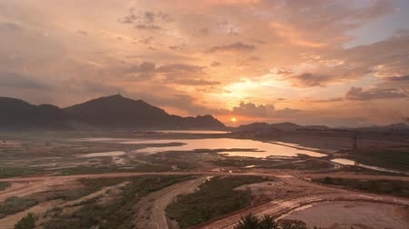 kapasite : Timelapse golden sunset at Mengkuang Dam during expansion to increase the capacity of water in dam. Excavation take place at the nearby area.