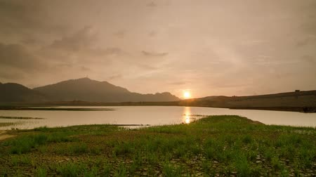 gát : Timelapse raining day at Mengkuang Dam. Beautiful golden cloud over  hill and crack land. Stock mozgókép