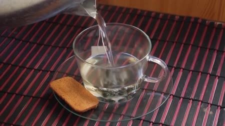 teacup : Preparing green tea in transparent teacup with digestive biscuit on a side