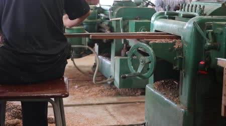 instrument maker : Rear view of worker is working with electric planer of wood machine.