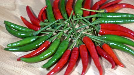 peperoni : fresh red and green chilli and chopped fresh red is rotating on wooden background