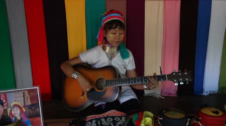lineage : Mae Hong Son, Thailand - November 9:Unidentified Karen Long Neck at the Ban Huay Sua Thao in Mae Hong Son, Thailand on November 9, 2014. Women playing guitar and singing karen song. Stock Footage