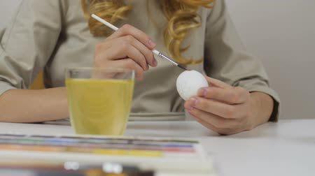 Unrecognizable woman paints Easter eggs with a brush. On the table is a glass of water and a bowl of eggs. Preparing for the holidays.
