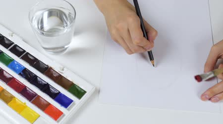Unrecognizable woman draws a pencil sketch on paper Easter card. On the table is a palette with paints and a glass of water.