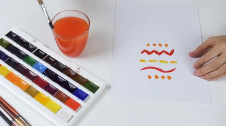 Unrecognizable woman paints a sketch with bright colors on paper for an Easter card. On the table is a palette with paints and a glass of water.