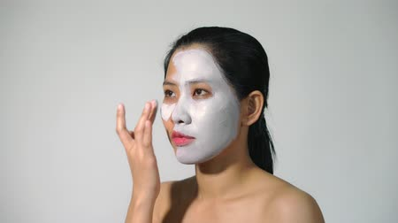 yumuşaklık : Young woman clay face mask peeling natural with purifying mask on her face on white background
