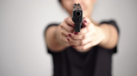 arma curta : young woman asian girl holding a gun aiming at the gun, with selective focus Vídeos