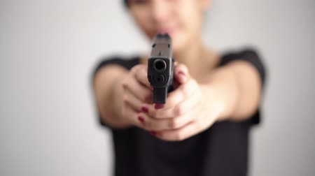 silahlar : young woman asian girl holding a gun aiming at the gun, with selective focus Stok Video