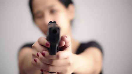 пистолеты : young woman asian girl holding a gun aiming at the gun, with selective focus Стоковые видеозаписи