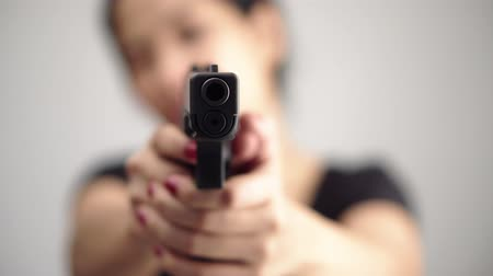 гангстер : young woman asian girl holding a gun aiming at the gun, with selective focus Стоковые видеозаписи