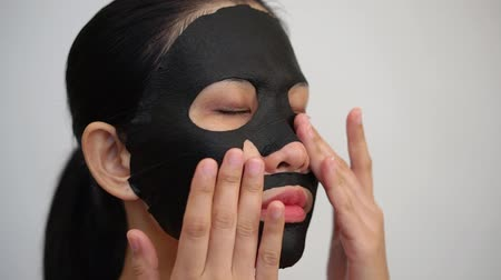 očistit : Young woman doing facial black mask sheet with purifying mask on her face on white background Dostupné videozáznamy