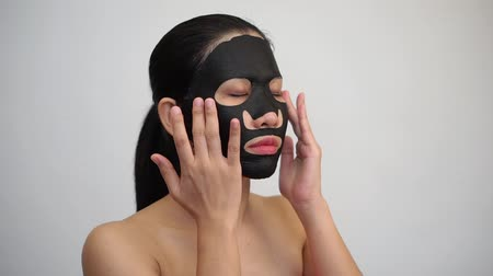 sheet : Young woman doing facial black mask sheet with purifying mask on her face on white background Stock Footage