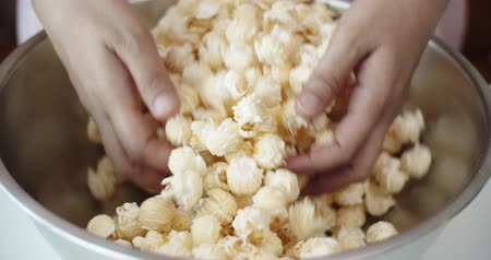 glicose : Close up mixing popcorn with their hands in the baking bowl, Slow Motion, 4K