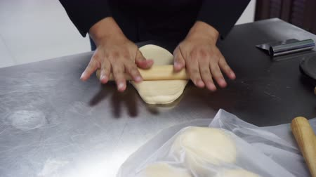 Chefs are using a dough roller to put the ham.