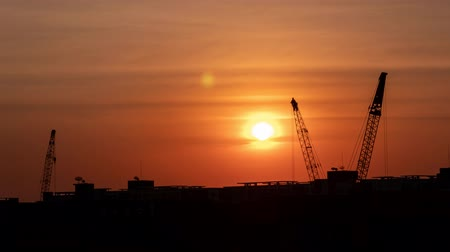 estaleiro : Time-lapse 4K: Cranes lifting containers background sunset in the evening.